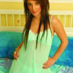 Bursa escort Galya kneeling on the bed and looking in the camera with huge brown eyes, her slender body is covered with thin translucent green nightgown with delicate lace, under which the subtle seductive panties are visible