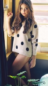 A girl delivering sex services in Bursa looks exceptionally mesmerizing in this sweater having long curly hair