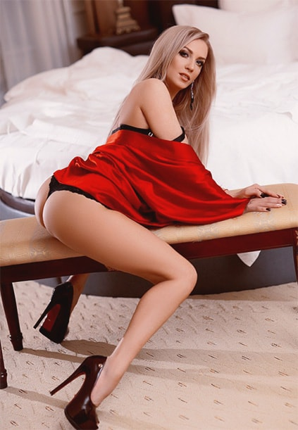 Escort Whatsapp dreamy lady Lera is sitting on top of a bench being dressed in red and black with seducing high heels