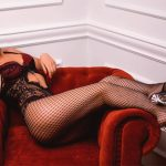 Escort Whatsapp affectionate maiden Polya sits in a blood-red upholstered chair exposing her slender figure