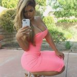 Eskortlar Bursa Alerina sits in a pink dress that completely makes her curves visible