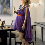 Outcall escort Bursa Lillian in violet with a glass of champagne in the room