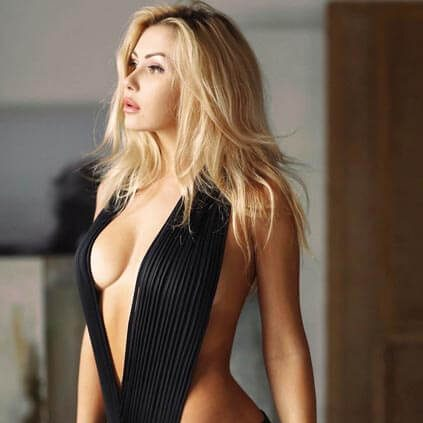 Blonde escort sex lady Nastya in the black stylish swimsuit is looking into the distance