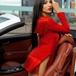 Russian blonde escort Carmen looks stunningly fabulous in a car's salon of chocolate-color leather