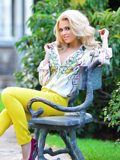 Blonde escorts Kristina in the yellow is sitting on a bench in a park