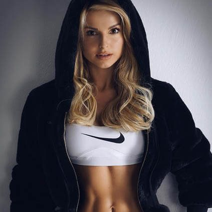 Mature blonde escort girl Lenochka in sports outfit looks at the camera giving an exciting look