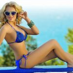Blonde escorts Kristina is sitting on a verge of a pool wearing sunglasses and smiling to you