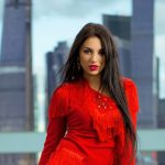 Russian blonde escort pussycat is in the background of a city wearing a red-hot passionate jacket