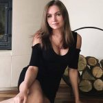 Incall escort service Kseniya in a simple attire is sitting near the fireplace smiling for you