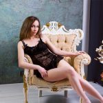 Outcall escorts Mashka sits back in a chair in a hotel room waiting for you